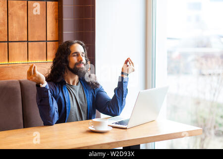 Portrait of successful handsome young adult man freelancer in casual style sitting in cafe with laptop, holding hands like meditation, have harmony, y - Stock Image
