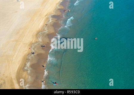 Benidorm, Costa Blanca, Spain, 29th November 2018. Sunbathers and swimmers enjoy the sun on Poniente beach. Average temperatures over 17 degrees Celsius through the winter months make the Costa Blanca an ideal destination for cold and wet Brits. An aerial view of poniente beach with surfer and walkers. Credit: Mick Flynn/Alamy Live News - Stock Image