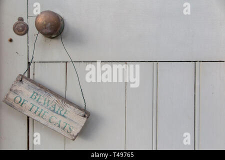 A sign warning to 'Beware of the Cats' on a weathered outside door - Stock Image