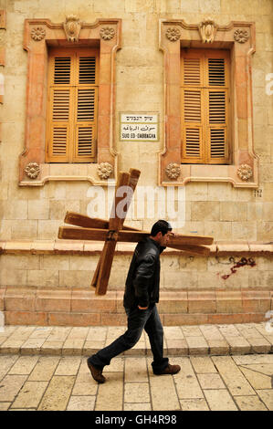 geography / travel, Israel, young Palestinian carrying rental crosses for pilgrims through the Via Dolorosa, Middle - Stock Image