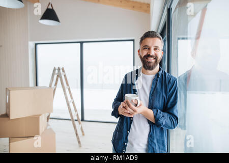 A mature man with cardboard boxes standing by a window, furnishing new house. - Stock Image