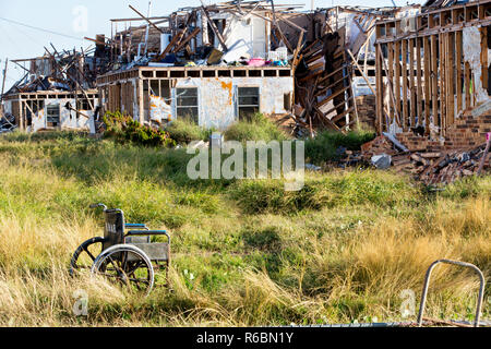 Apartment complex (two story units) destroyed by hurricane Harvey 2017, abandoned wheelchair. - Stock Image