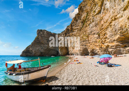 A boat waits on the sandy beach to transport tourists back to town from the Paradise Beach, also known as Chomi Beach, on the island of Corfu Greece - Stock Image