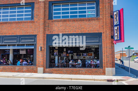 JOHNSON CITY, TN, USA-4/27/19: Customers seen dining through windows of the Wild Wing Restaurant, while an employee sweeps the curb outside. - Stock Image