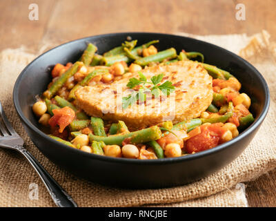 Green Bean and Tomato Stew with Chickpeas and a Vegan Cutlet. Based on a Lebanese recipe (Loubieh bi zait). - Stock Image