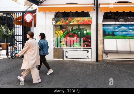 Two women walking in the Feria Market in Seville - Stock Image