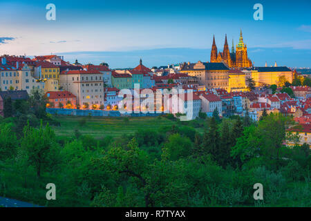 Prague Hradcany, early evening view from above the Petrin Park treeline towards the Hradcany Castle district in Prague, Czech Republic. - Stock Image