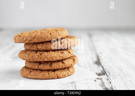 Stack of fresh homemade oatmeal cookies with a bottle of milk on a white table against a white background.. - Stock Image