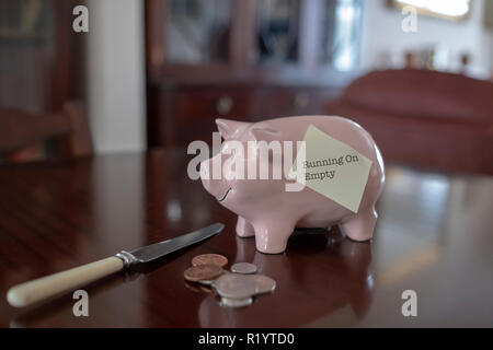 Piggy bank on polished table with loose change and knife and post it note saying running on empty - Stock Image