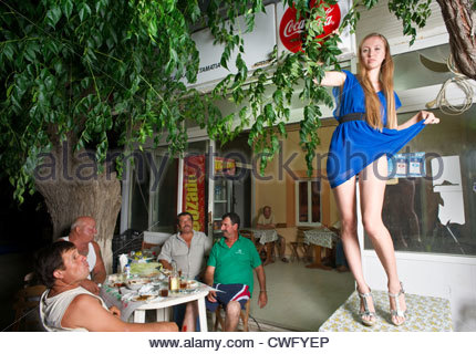 Europe, Greece, View Of Young Woman Dancing On Cafe Table Wearing A Blue Dress, Showing Her Legs To Group Of Male - Stock Image