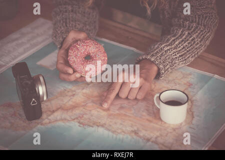 Close up of traveler woman hands planning the next trip vacation with a paper map - old camera and coffee on the table - breakfast time with donuts -  - Stock Image