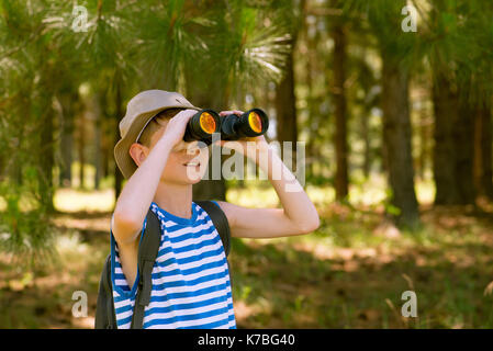 Boy using binoculars in woods - Stock Image