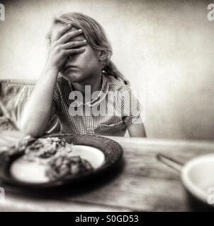 Child struggling/refusing to eat dinner. Girl, 7 years. - Stock Image