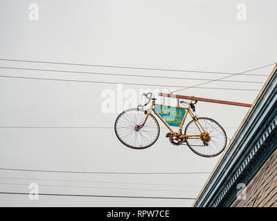 Bicycle shop sign attached to a suspended bicycle over the exterior front entrance to the business, a unique advertising idea, in Montgomery Alabama. - Stock Image
