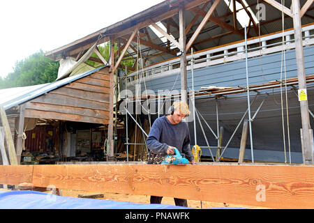 Ned Rolf (son of Peter Rolf boat builder)using a modern power plane to true up the 45ft sold main boom to convert the mast from square to round, Truro - Stock Image