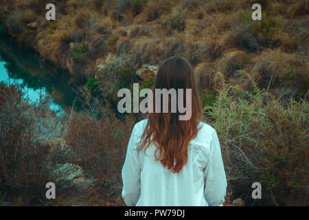 Young caucasian woman with long chestnut hair in white linen shirt looks at river standing in field meadow. Cozy autumn atmosphere. Beautiful landscap - Stock Image