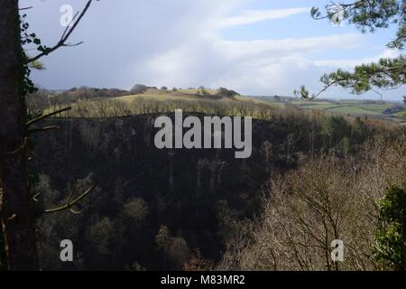 View across the steep woooded slopes of Cwm Wyre to Pen Rhos iron age hillfort, settlement, Llanrhystud, Wales, - Stock Image