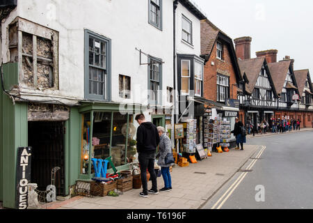Shopers looking at antique junk items for sale outside an old Antiques shop in the High Street, Arundel, West Sussex, England, UK, Britain - Stock Image