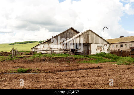 Rural farm buildings in Russia during the summer sun - Stock Image