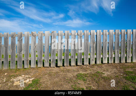 Picket fence constructed of bare unpainted timber on barren ground with blue sky and clouds. - Stock Image