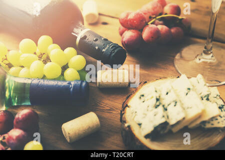wine bottles grapes and cheese on old wooden table - Stock Image