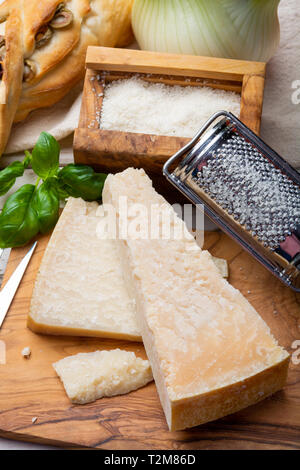 Original italian cheese, aged Parmesan cow milk cheese, pieces and grated Parmigiano-Reggiano close up - Stock Image