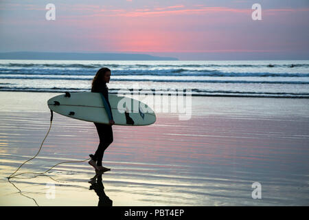 Young female surfer carrying her surfboard as she heads off in to the sea to catch a wave surfing at Westward Ho! beach, North Devon, England, Europe. - Stock Image