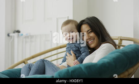 Low angle selective focus portrait of mother and baby son posing and sitting in chair - Stock Image