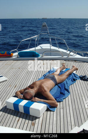 Man tans on the sun on a yacht on the background of the Red Sea, Egypt - Stock Image
