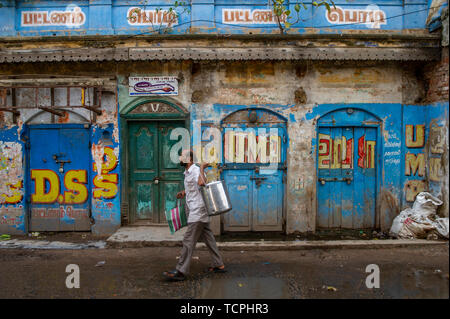 Poverty in Chennai, India, where a shopper carries his tea urn - Stock Image