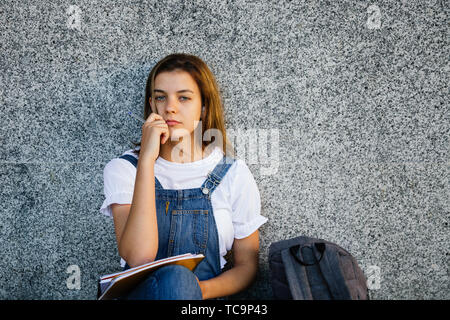 Pensive teen student girl in denim overalls studying and listening to music sitting on the floor - Stock Image