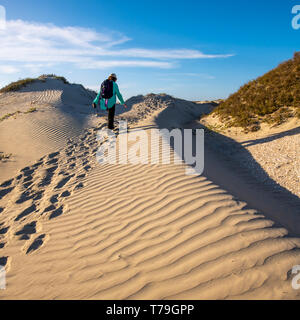 Woman with backpack hiking up sand dune on a sunny day on Isla Magdalena, Baja California Sur, Mexico. - Stock Image