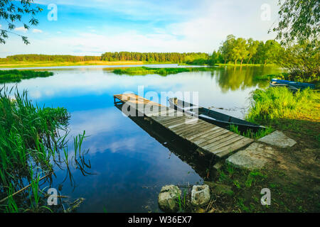Fishing pier on the river a picturesque landscape with a boat. Summer - Stock Image