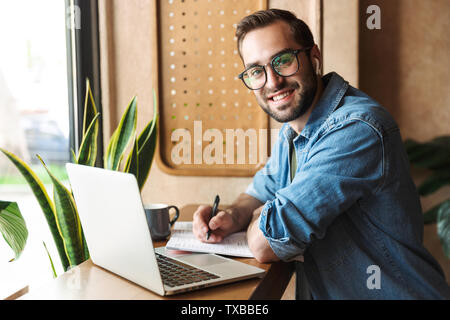 Photo of attractive smiling man wearing glasses writing and using earpod with laptop while working in cafe indoors - Stock Image