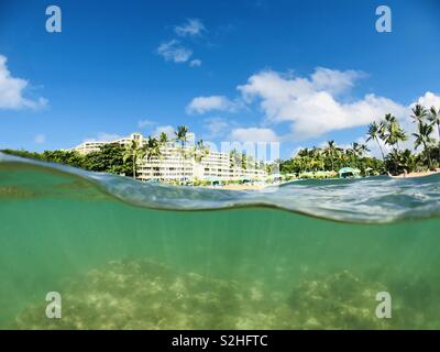 Over under photo from the water of the St. Regis Princeville resort while snorkeling. Princeville, Kauai, Hawaii USA. - Stock Image