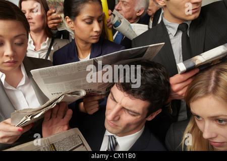 Businesspeople reading newspapers on crowded train - Stock Image