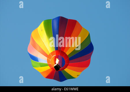 A colourful hot air balloon in flight with its burner firing and blue sky behind during the Bristol Balloon fiesta - Stock Image