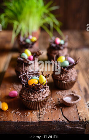 Easter nest cupcakes with chocolate whipped cream, decorated with colorful eggs - Stock Image