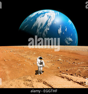 A marooned astronaut looks up at an alien sun that illuminates the barren world he stands on. A large water covered - Stock Image