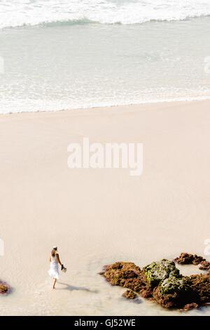 A woman walking along Wategos Beach in Byron Bay. - Stock Image
