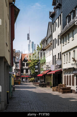 Quaint cobblestone street in Sachsenhausen, with Commerzbank skyscraper tower in the background, Frankfurt am Main, Hesse, Germany. - Stock Image