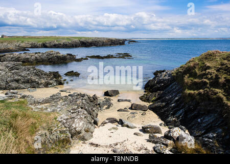 Small sandy beach in a rocky cove between Borthwen and Silver Bay, Rhoscolyn, Isle of Anglesey, Wales, UK, Britain - Stock Image