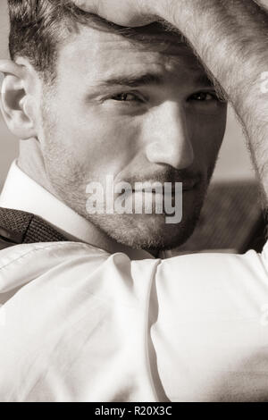 Portrait of good looking man wearing white shirt and waistcoat, looking at camera - Stock Image
