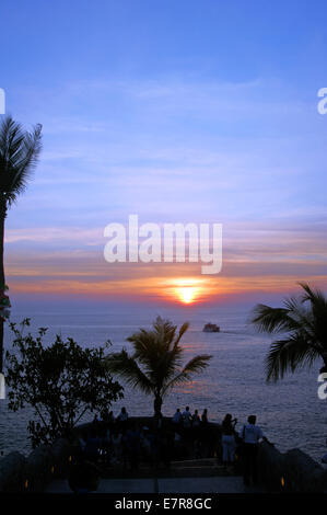 A small boat sails off into the sunset in Acapulco - Stock Image