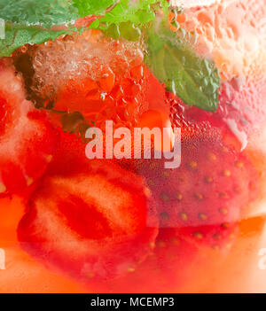 background pitcher of strawberry lemonade with water drops close-up - Stock Image
