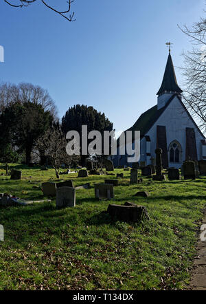 Gravestones in from on a backlit St Mary the Virgin church in Northolt Village, Middlesex, UK - Stock Image