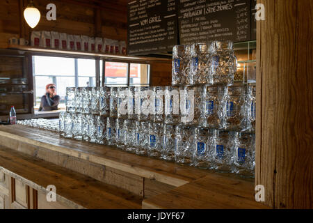 Berlin, Germany - June 10 2017: Typical German pub interior, woman looking through the window. - Stock Image