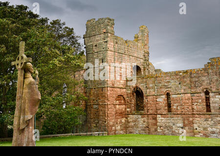 Life size statue of St Aidan first bishop of Lindisfarne facing ruins of the medieval priory on Holy Island of Lindisfarne England UK - Stock Image