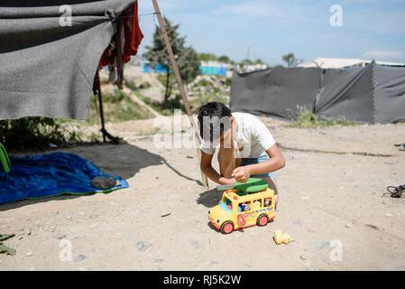 Eine Junge lässt die Zeit still stehen während er mit einem Spielzeug Auto spielt. Flüchtlingscamp von Idomeni in Griechenland an der Grenze nach Maze - Stock Image