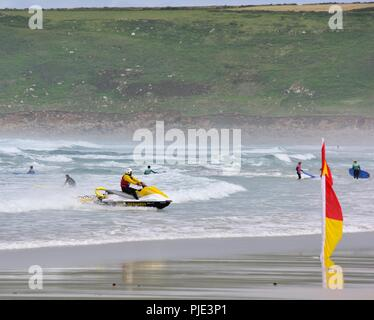 RNLI Lifeguard approaching the beach on rescue jet ski,Sennen Cove,Cornwall,England,UK - Stock Image